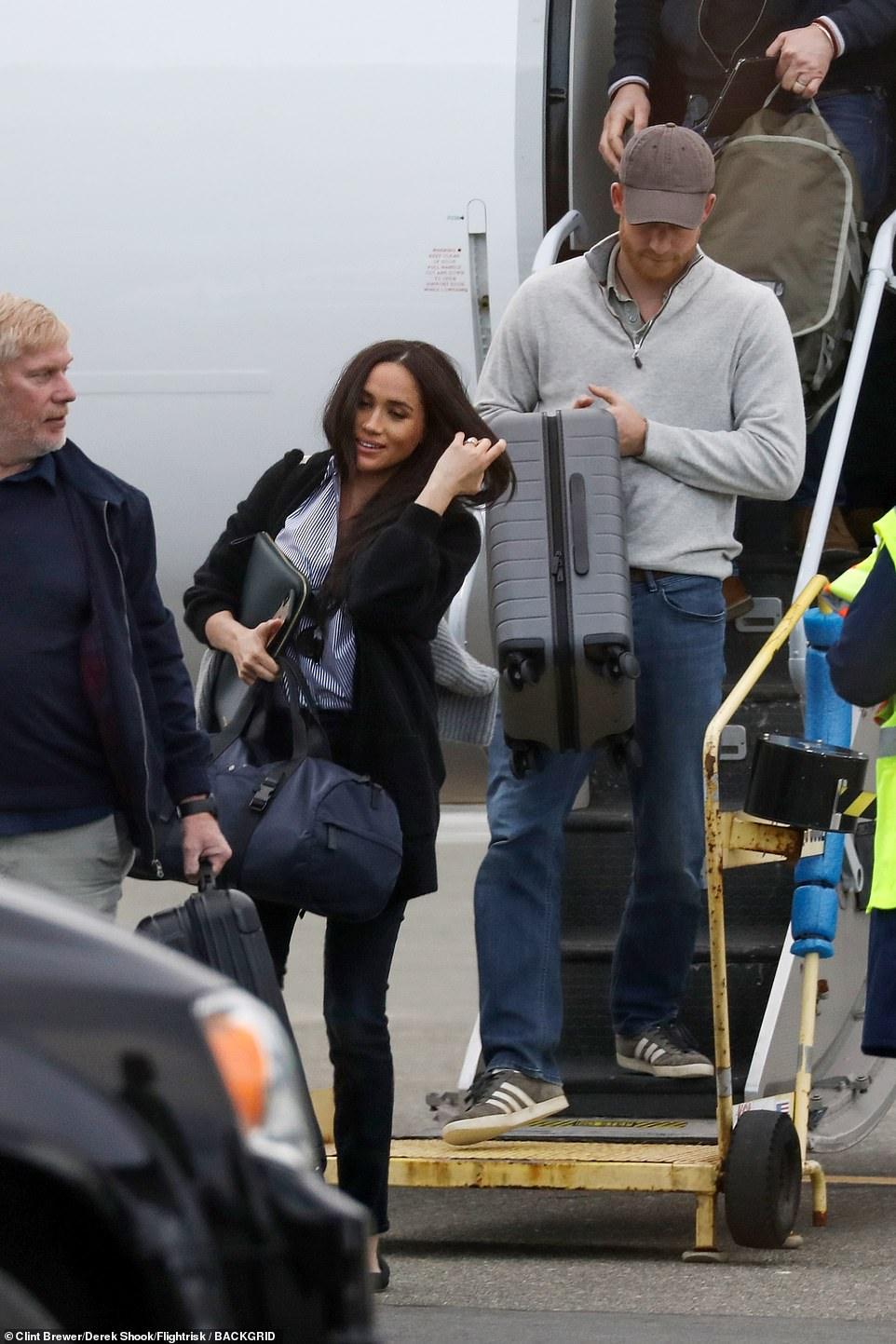 La pareja real sonríe con sus propias maletas en un vuelo comercial en Canadá